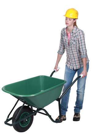 wheelbarrow: Woman pushing empty wheelbarrow Stock Photo