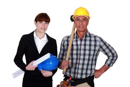 servicewoman: studio shot of young female architect and mature carpenter Stock Photo