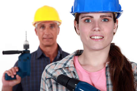 constructors: Man and woman holding power drills