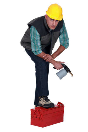 casualness: Tradesman posing with his foot propped on a toolbox and holding a spray gun Stock Photo