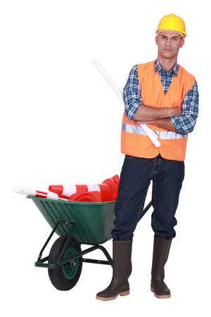 grouch: Angry tradesman standing in front of a wheelbarrow Stock Photo
