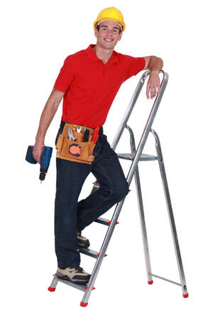 rungs: Young tradesman standing on a stepladder and holding a screw gun Stock Photo