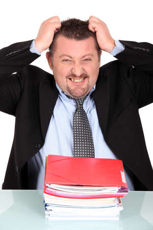 Businessman tearing his hair out over a pile of paperwork Stock Photo - 17904407