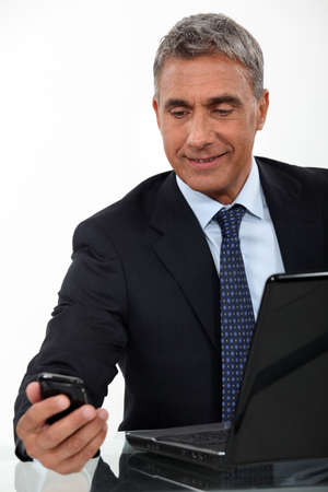 Mature businessman with a laptop and cellphone photo