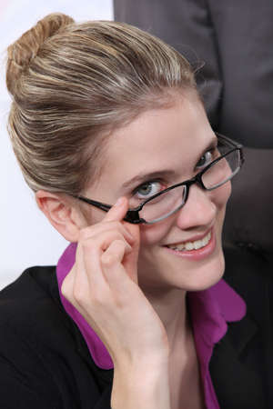 Cheerful blond bussineswoman touching her glasses photo