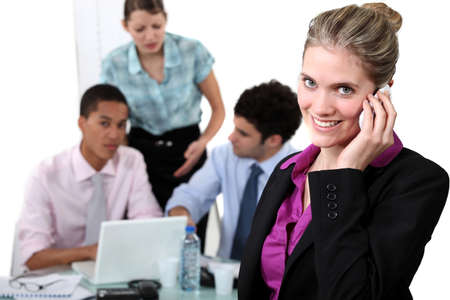 Smiling woman taking a call in front of busy colleagues photo