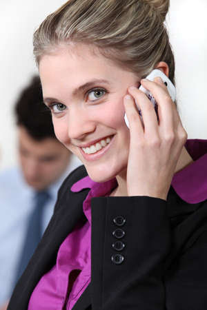 highlighted hair: Smiling businesswoman taking on her mobile phone