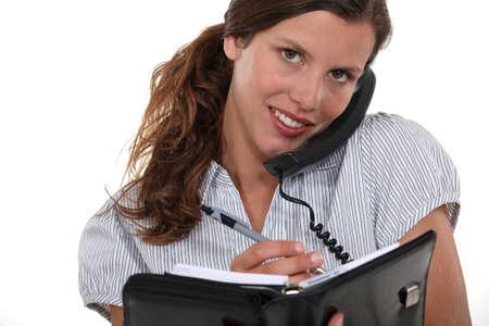 tertiary: pretty businesswoman on the phone holding agenda Stock Photo