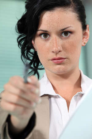 Close-up shot of a woman pointing her pen Stock Photo - 17977058