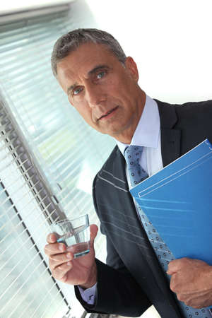 Businessman holding glass of water and folder Stock Photo - 17977064