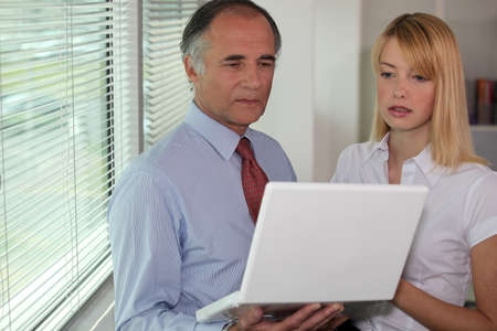 uneasiness: Businessman looking at a laptop with his assistant Stock Photo