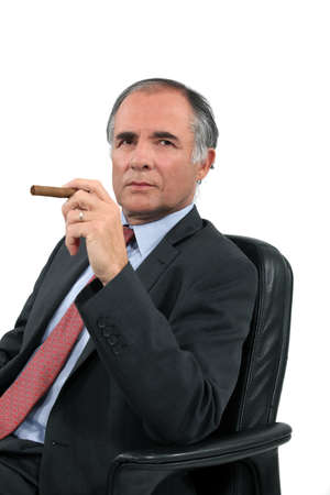 hombre fumando puro: Hombre de negocios con un cigarro