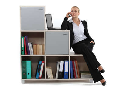 bookish: Woman sitting on a bookcase Stock Photo