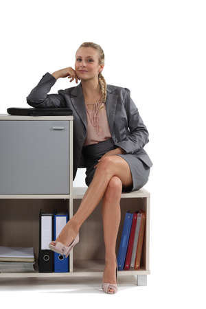 legs crossed at knee: Businesswoman sitting on a storage unit Stock Photo