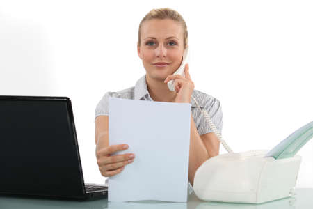 Woman at her desk using fax photo