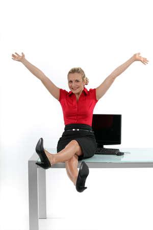 beine spreizen: Entspannte Frau sitzt auf ihrem Schreibtisch