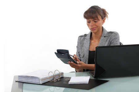 indeterminate: Businesswoman using a calculator at her desk Stock Photo