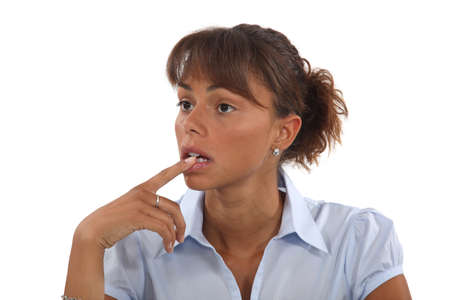 Confused woman holding finger to mouth Stock Photo