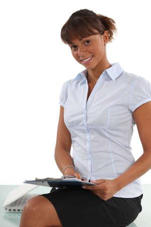 secretary desk: Secretary perched on a desk with a clipboard Stock Photo