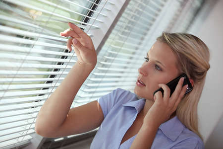 waiting glance: Businesswoman peering through blinds during call