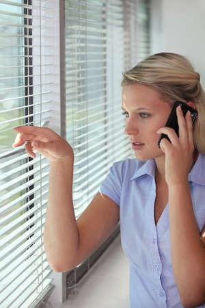 Woman on the phone looking through venetian blinds photo