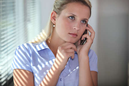 Young woman using a cellphone in an office Stock Photo - 17977269