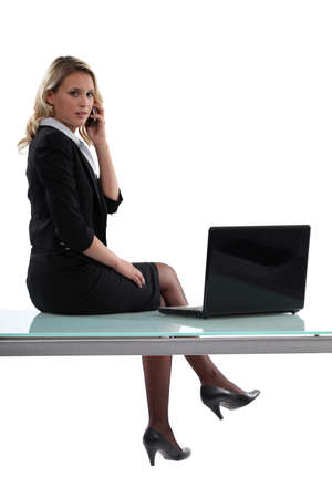 Sexy businesswoman assis sur un bureau photo