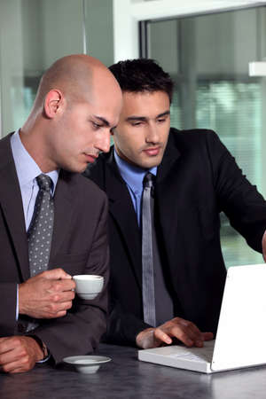 conspiratorial: Businessmen looking at a laptop