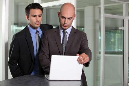 collaborators: Two businessmen in hallway