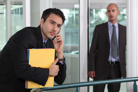 businessman looking at male colleague in workplace Stock Photo - 17977519