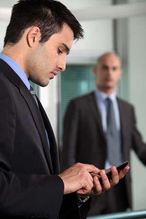 send sms: Businessman sending a text message