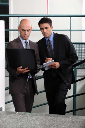 collaborators: Businessmen comparing notes in stairwell