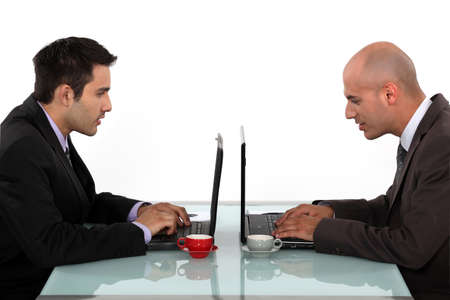 collaborator: Profile of businessmen working at their laptops Stock Photo