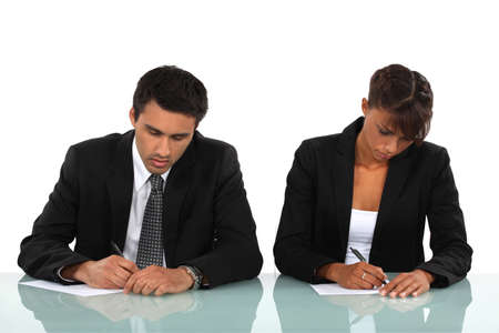 Two business people writing at a desk Stock Photo - 17976513