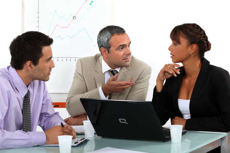 businessmeeting: Three people in animated business meeting Stock Photo
