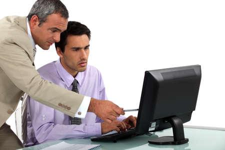 glitch: L'uomo indicando un errore al suo collega Archivio Fotografico
