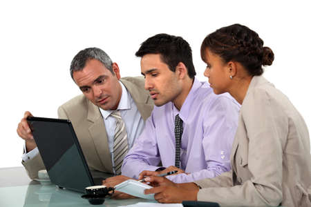 Business people looking at a laptop photo