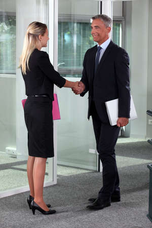 businessmen shaking hands: businessman and businesswoman shaking hands
