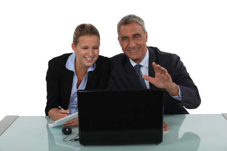 Business couple laughing at a laptop photo