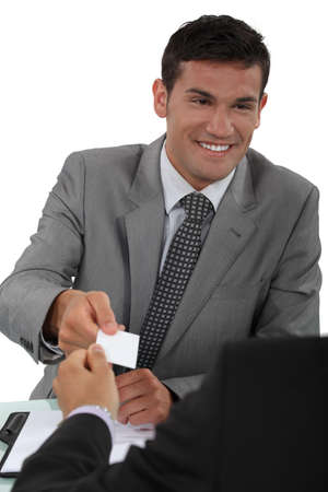 personalised: Man handing over his business card to a potential client Stock Photo