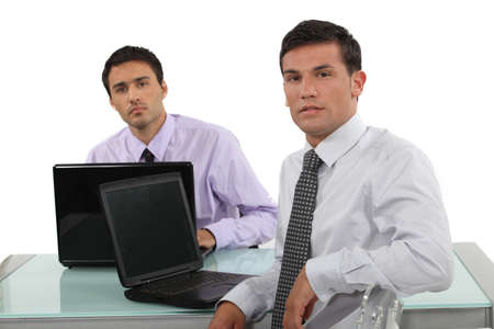 Two businessmen sat at the same desk photo
