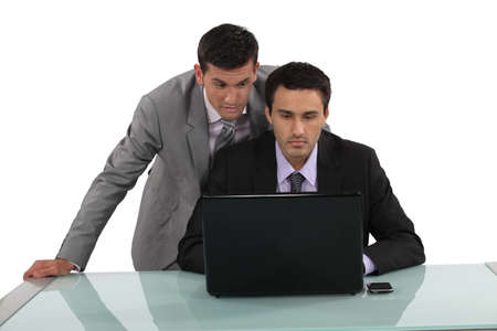 banter: Businessmen looking at a laptop