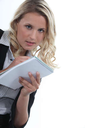 eager: Blond office worker writing on note pad