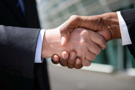 diplomacy: Businessmen shaking hands outdoors