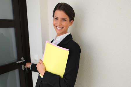 Female estate agent putting key in door photo
