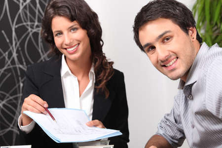 Saleswoman showing client where to sign photo