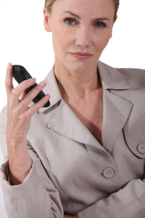 Serious woman holding a mobile phone photo