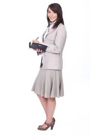 pencil skirt: Woman in a skirt suit writing in a personal organizer