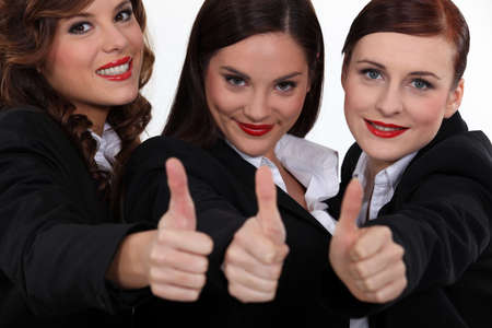 Three corporate women giving the thumbs-up photo