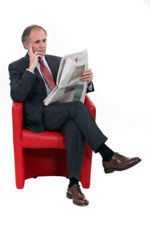 isolated chair: Mature businessman with a newspaper